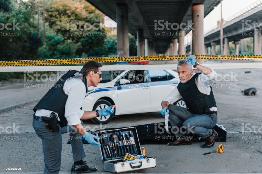 male police offier with clipboard talking to colleague in sunglasses near corpse in body bag at crime scene stock photo