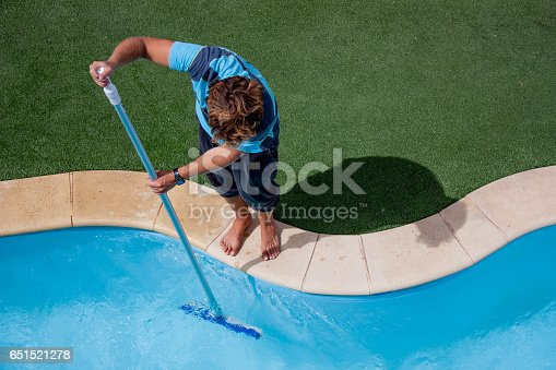 Pool guy celaning a pool with vacuum cleaner
