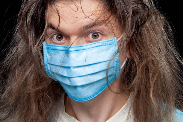 male portrait in a medical mask with a crazy look and disheveled hair on his head, closeup. - covid hair imagens e fotografias de stock