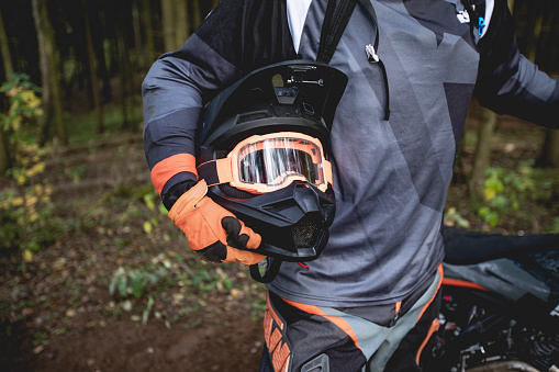 Male portrait of motocross enduro rider outdoors. Sports concept for motorsport on sports track. Professional biker with helmet and stunt motorcycle. Man with protective sportswear.
