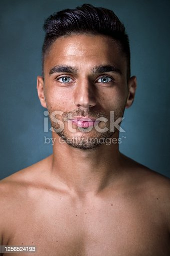 Handsome man portrait, posing shirtless looking at camera against gray-blue background
