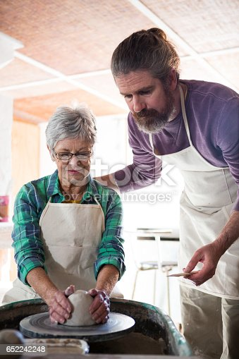 652188430 istock photo Male potter assisting female potter while making pot 652242248