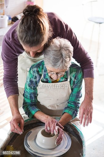 652188430 istock photo Male potter assisting female potter while making pot 652242286