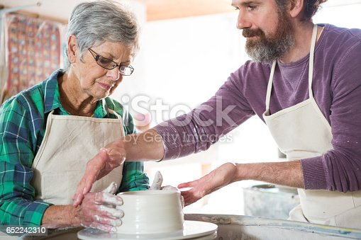 652188430 istock photo Male potter assisting female potter while making pot 652242310