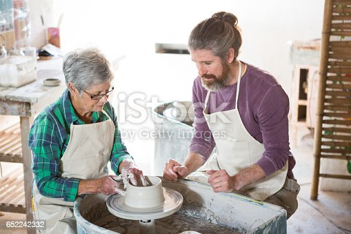 652188430 istock photo Male potter assisting female potter while making pot 652242332