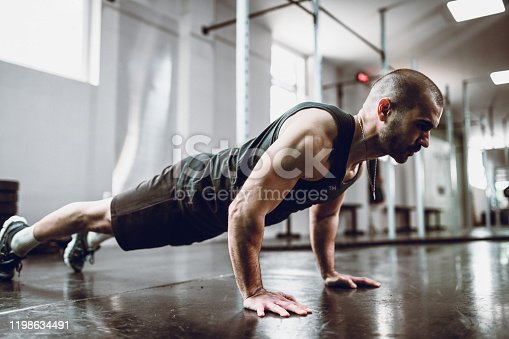 Male Practicing Pushups In Gym
