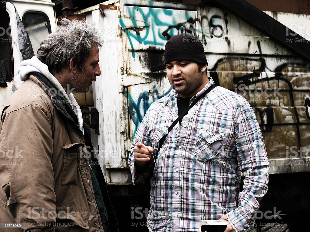 Male Preaching to a Homeless Man royalty-free stock photo