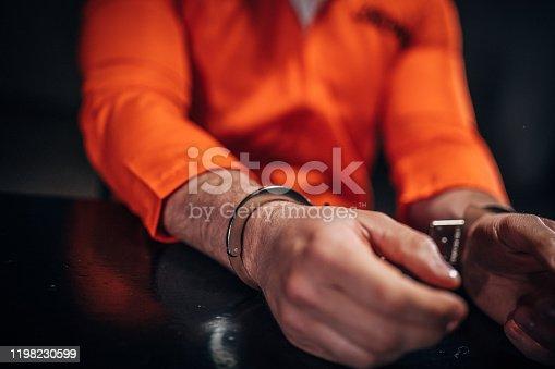 One man, prisoner in orange jumpsuit wearing handcuffs in dark room.