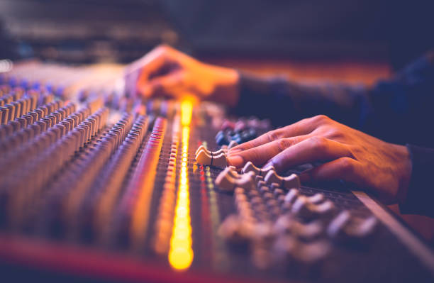 male producer, sound engineer hands working on audio mixing console in broadcasting, recording studio male producer, sound engineer hands working on audio mixing console in broadcasting, recording studio recording studio stock pictures, royalty-free photos & images