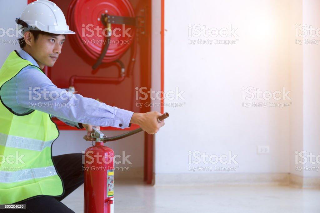 Masculino profissional verificando um extintor de incêndio. - foto de acervo
