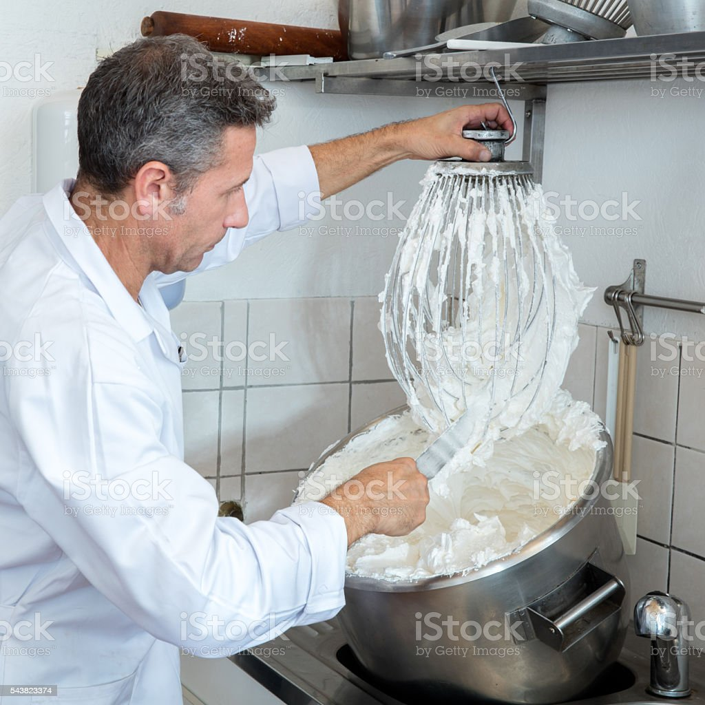 male professional cook cleaning big whisk to prepare french