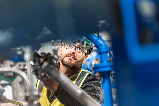 Hombre de examinar la máquina en fábrica profesional - foto de stock