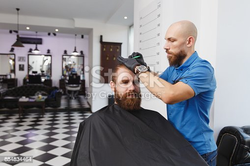986804130istockphoto Male professional hairdresser serving client by clipper. Ginger handsome brutal stylish young man with thick big beard and short hair getting trendy haircut in black cape. Light white barber shop room 884834464