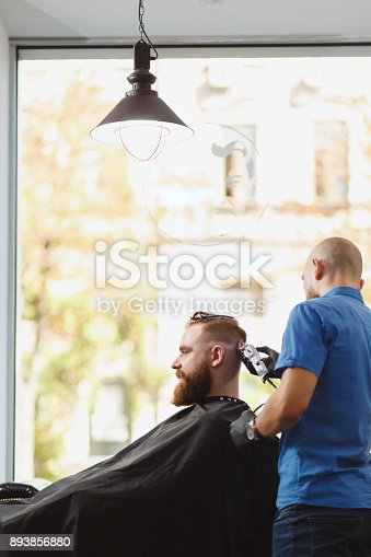 986804130istockphoto Male professional hairdresser serving client by clipper. Ginger handsome brutal stylish young man with thick big beard and short hair getting trendy haircut in black cape. Light white barber shop room 893856880