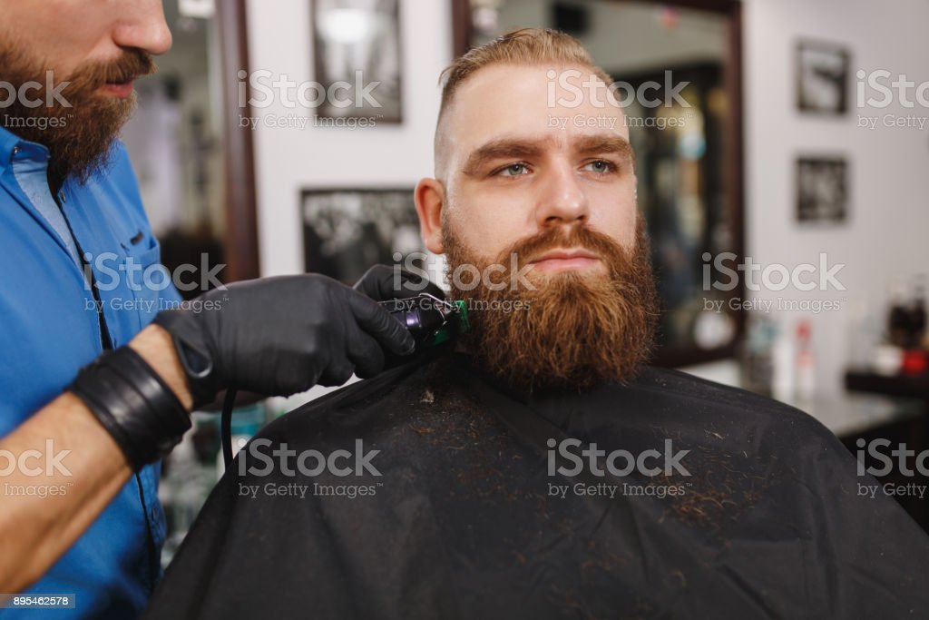 Male Professional Hairdresser Serving Client By Clipper. Ginger Handsome  Brutal Stylish Young Man With Thick