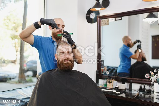 986804130istockphoto Male professional hairdresser serving client by scissors. Ginger handsome brutal stylish young man with thick big beard, short hair getting trendy haircut in black cape. Light white barber shop room. 885944314