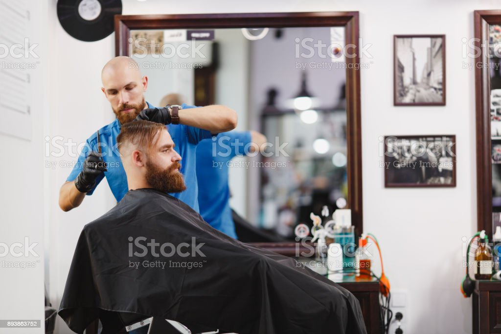 Male Professional Hairdresser Serving Client By Scissors. Ginger Handsome  Brutal Stylish Young Man With Thick