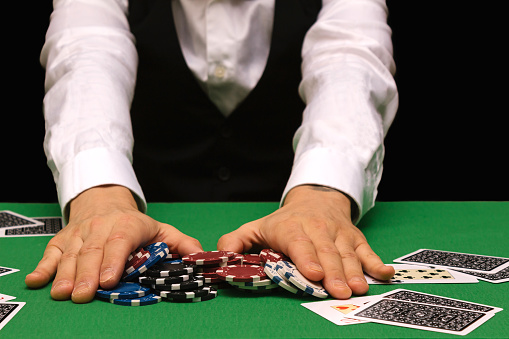 Male professional poker player placing a bet playing the game of poker in a casino with green baize and black copy space. Ruined concept, online winner.
