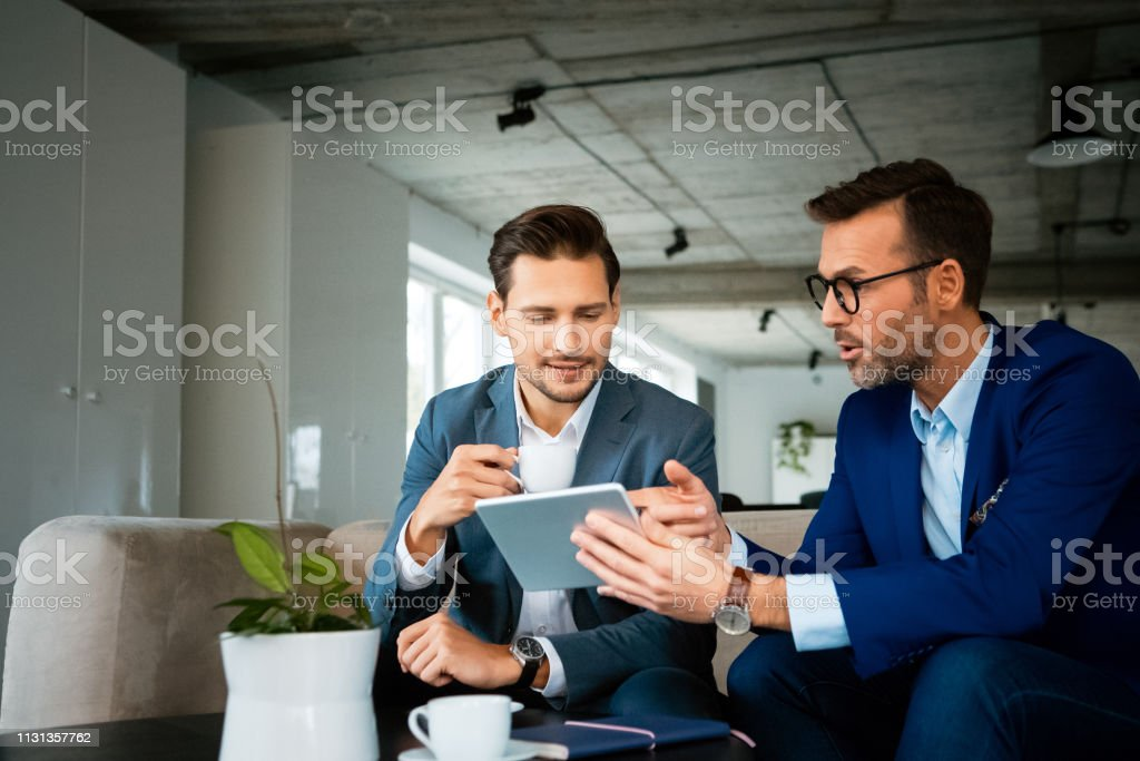 Male professionals discussing over digital tablet Confident male professionals discussing over digital tablet. Colleagues are planning strategy during meeting. They are working at creative office. 30-39 Years Stock Photo