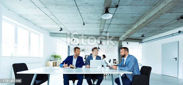 Team of male professionals discussing over document during meeting. Entrepreneurs are planning strategy at desk. Businessmen are working at creative office.