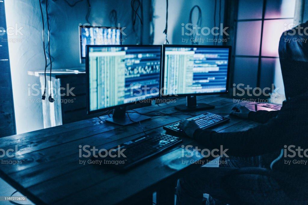 Male programmer working on desktop computer at desk in office in dark