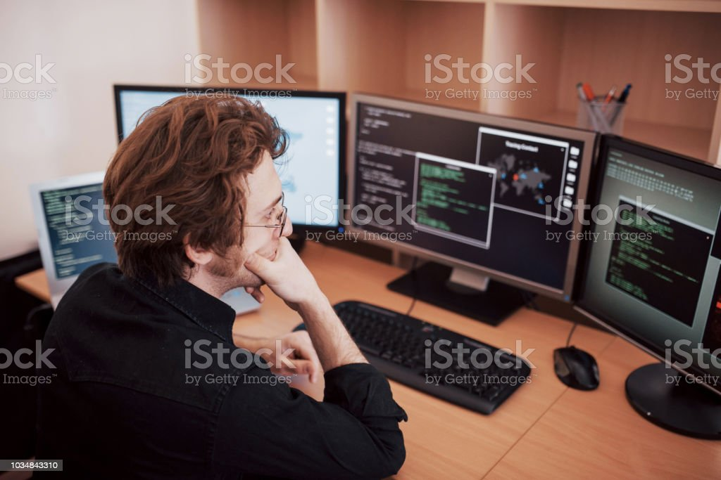 Male programmer working on desktop computer with many monitors at...