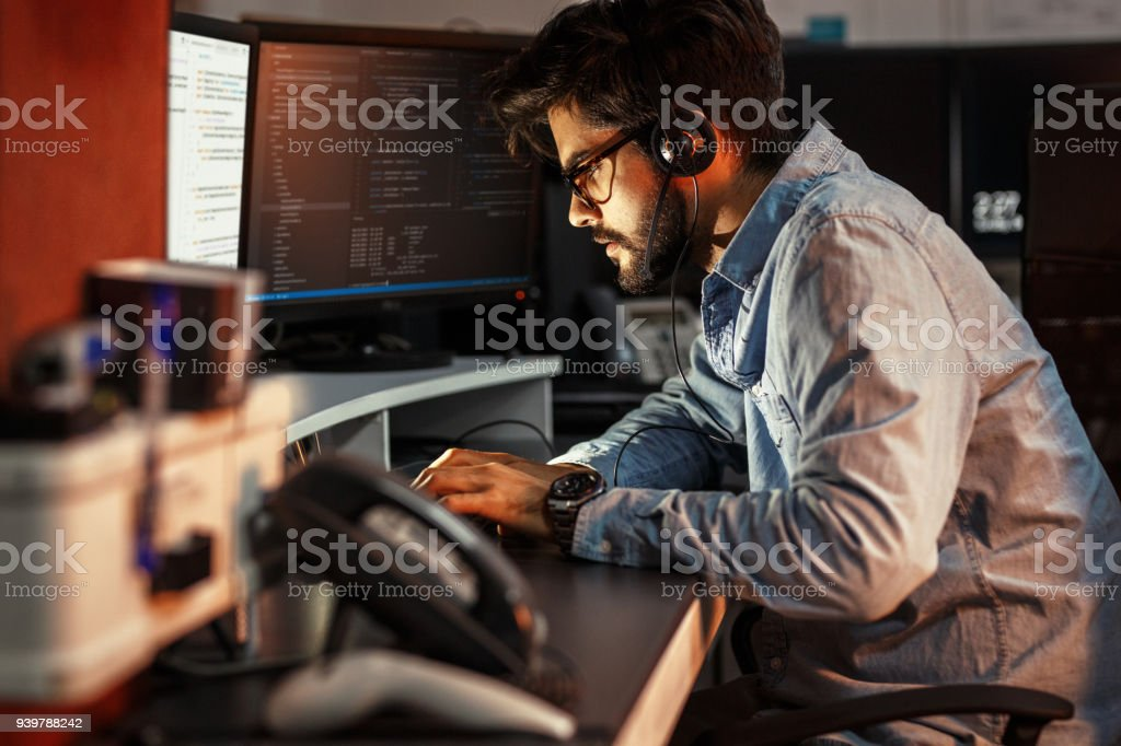 Male programmer working on new project.He working late at night at the office. stock photo