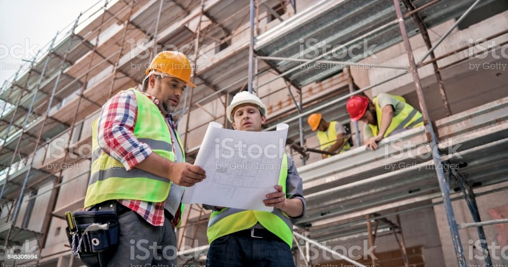 Male project superintendent discussing plans with foreman at construction site stock photo