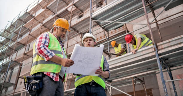 Male project superintendent discussing plans with foreman at construction site Male project superintendent and male foreman discussing plans at construction site wearing safety helmets. construction superintendent stock pictures, royalty-free photos & images