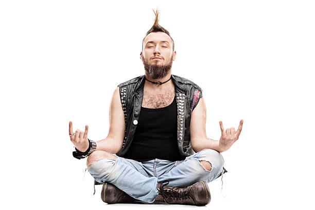 male punk meditating seated on the floor - punk music stock photos and pictures