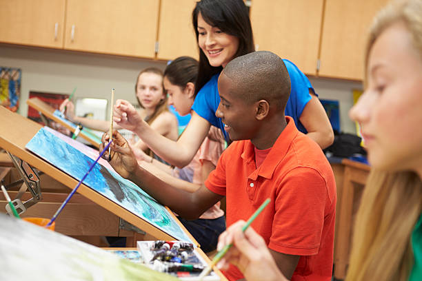 Male Pupil In High School Art Class With Teacher stock photo