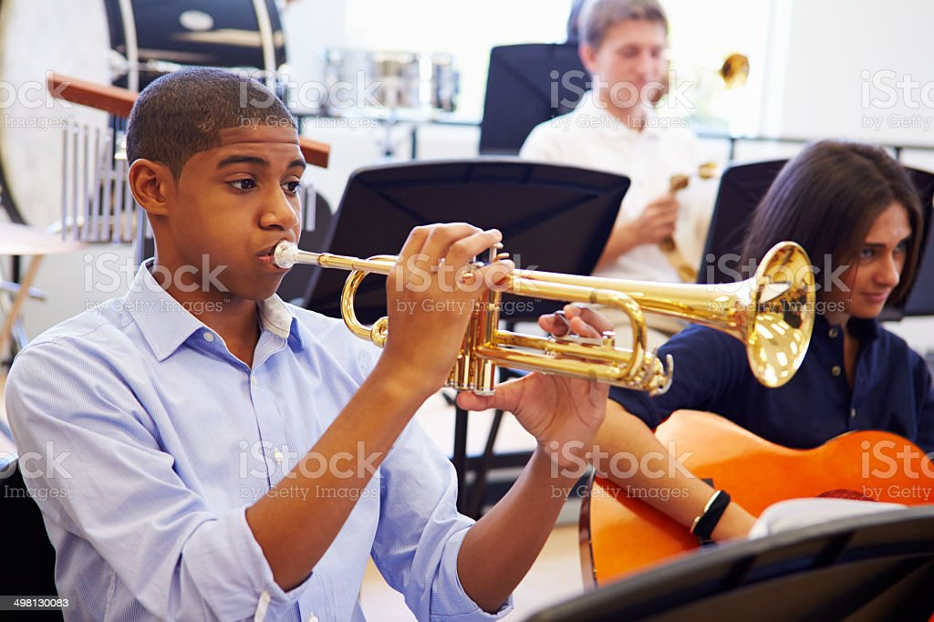 Male Pupil Playing Trumpet In High School Orchestra royalty-free stock photo
