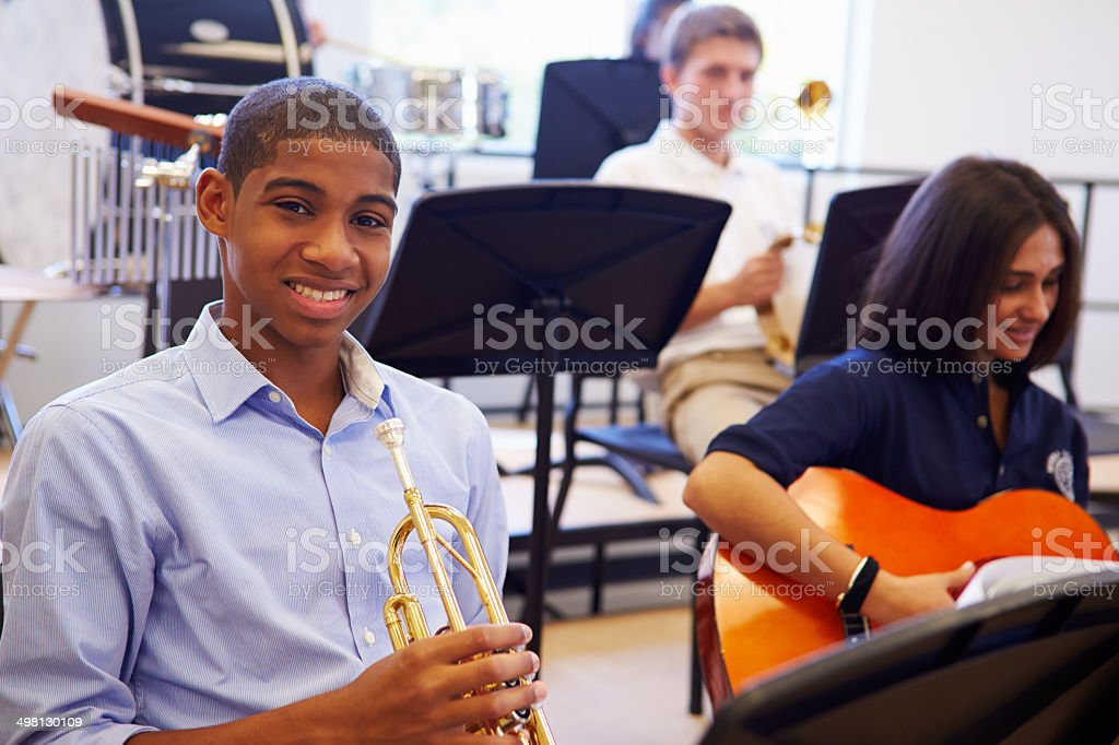 Male Pupil Playing Trumpet In High School Orchestra stock photo