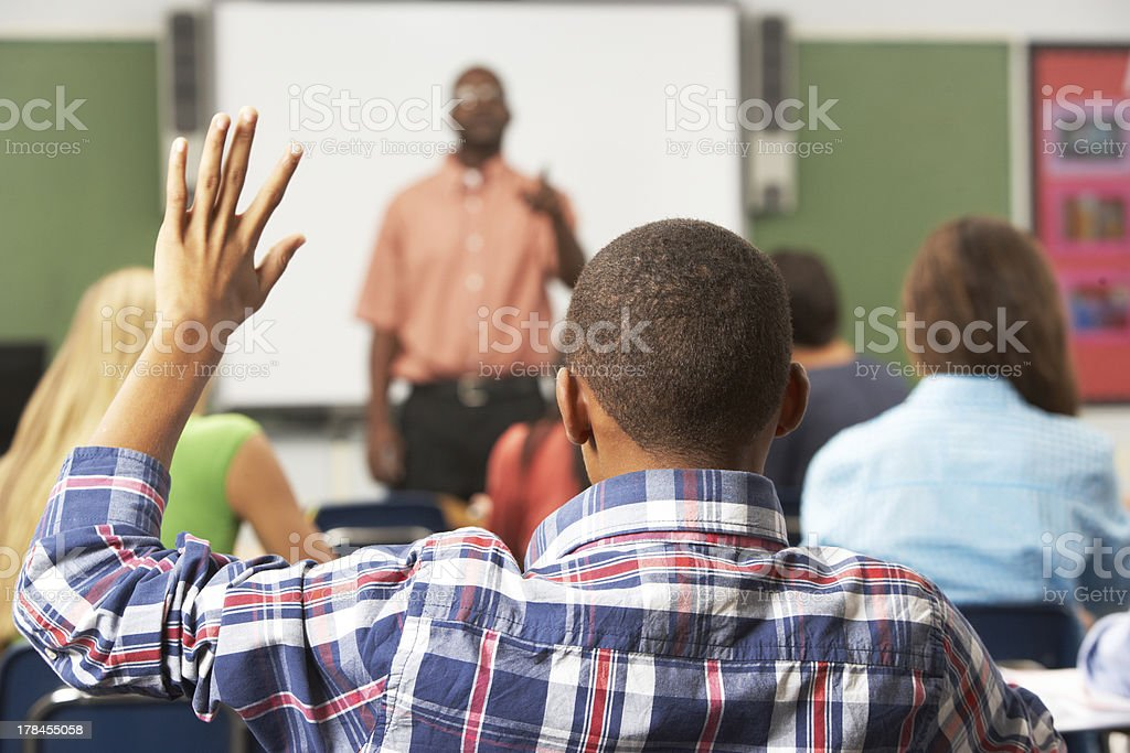 Male Pupil Raising Hand In Class royalty-free stock photo