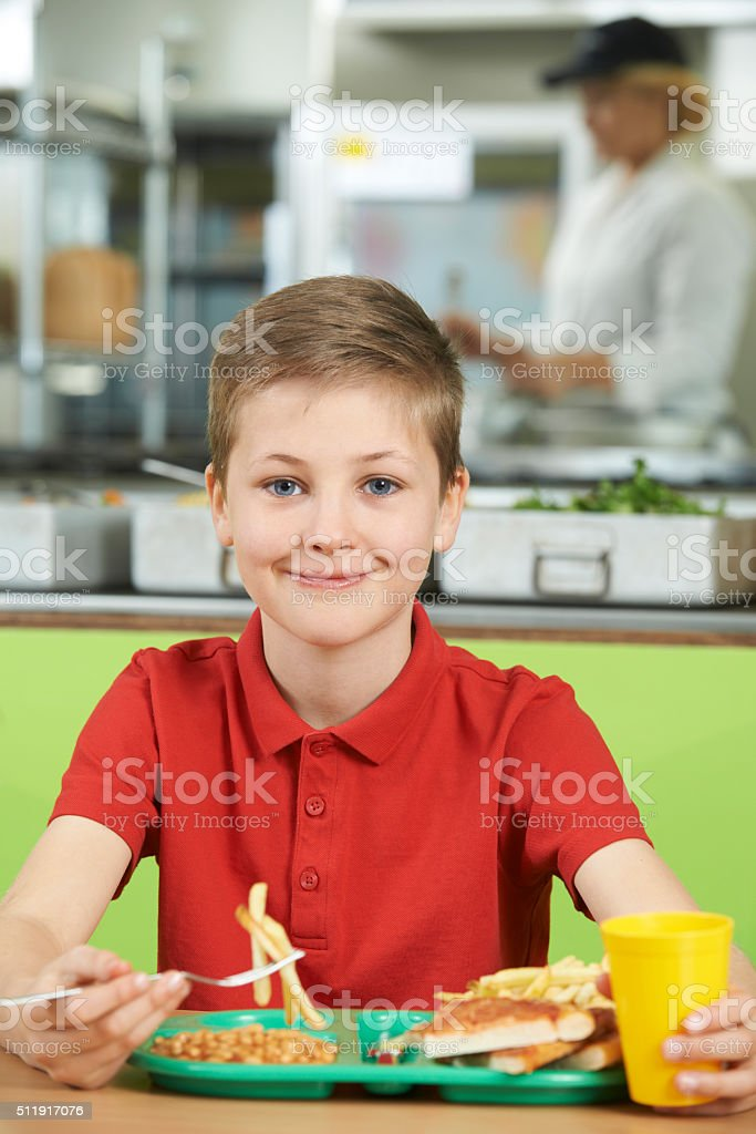 Male Pupil Sitting At Table In School Cafeteria Eating Unhealthy stock photo