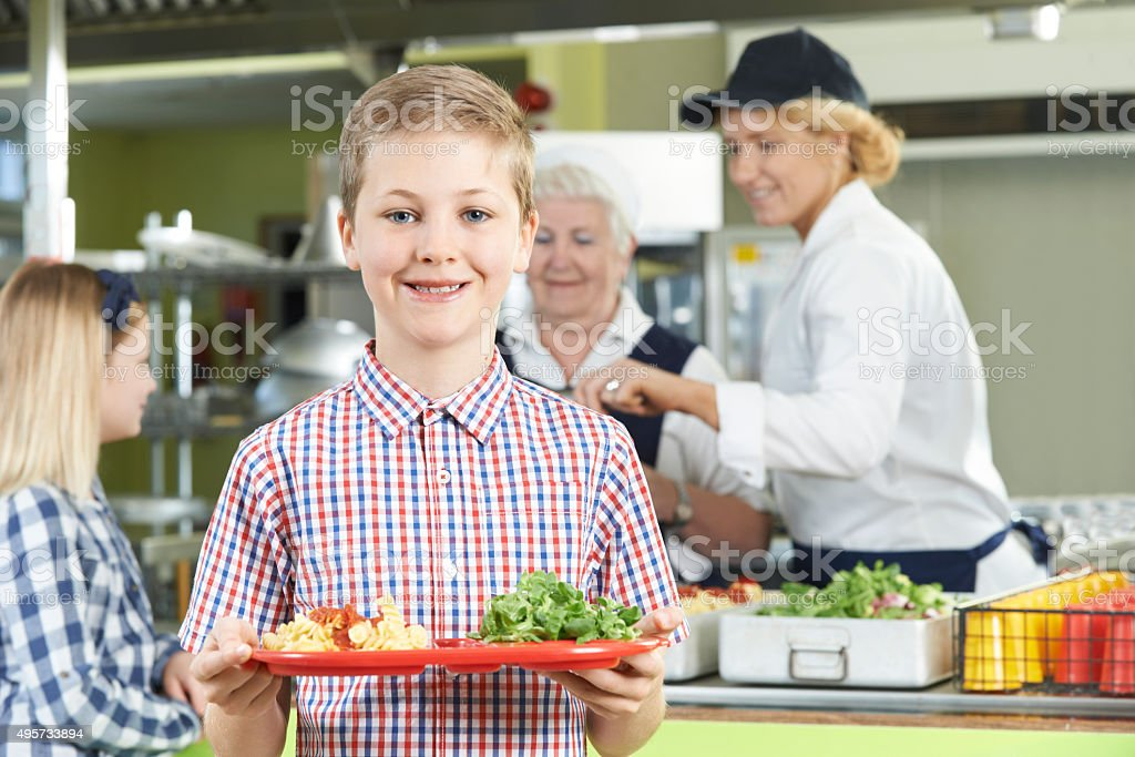 Male Pupil With Healthy Lunch In School Canteen stock photo