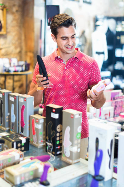 male purchaser touching sexy toys in the modern sex shop Glad cheerful  smiling male purchaser touching sexy toys in the modern sex shop sex toy stock pictures, royalty-free photos & images