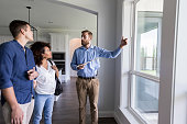 Confident male realtor shows potential homeowners a view from the living room windows in the home.