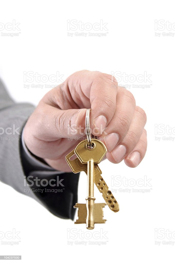 Male real estate executive hand holding two keys. royalty-free stock photo