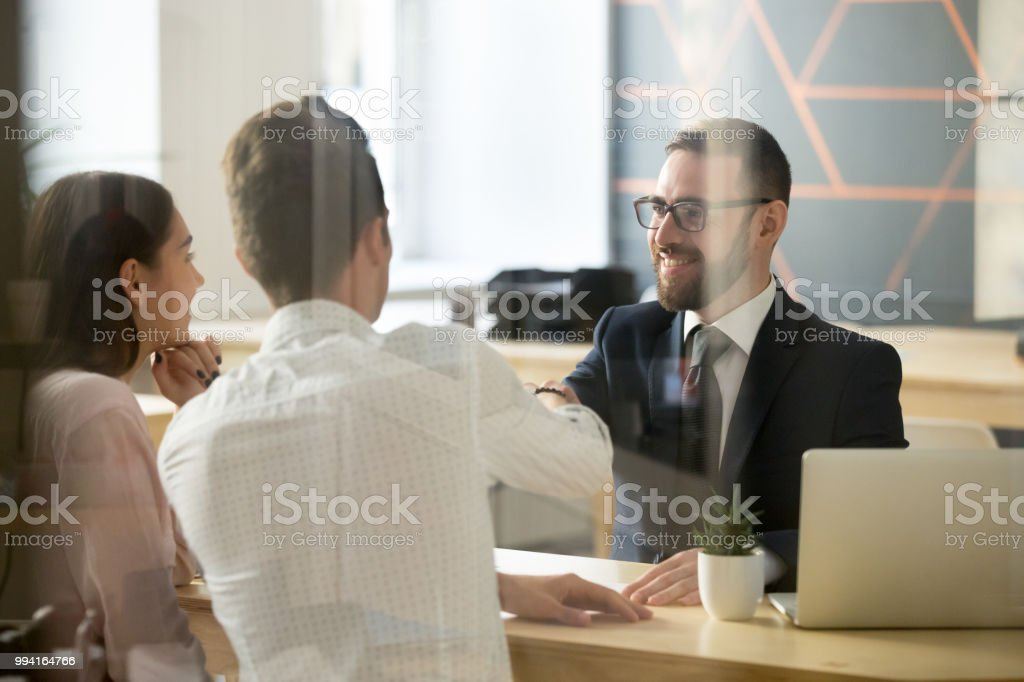 Male realtor handshaking clients after successful negotiations in office Smiling male realtor or broker shaking hand of excited buyers couple, negotiating about first house purchase or taking loan, insurance agent welcoming clients with handshake at consultation meeting Adult Stock Photo