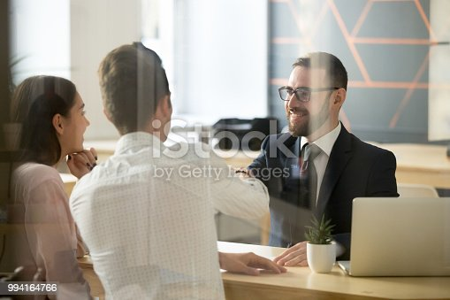 994164754 istock photo Male realtor handshaking clients after successful negotiations in office 994164766