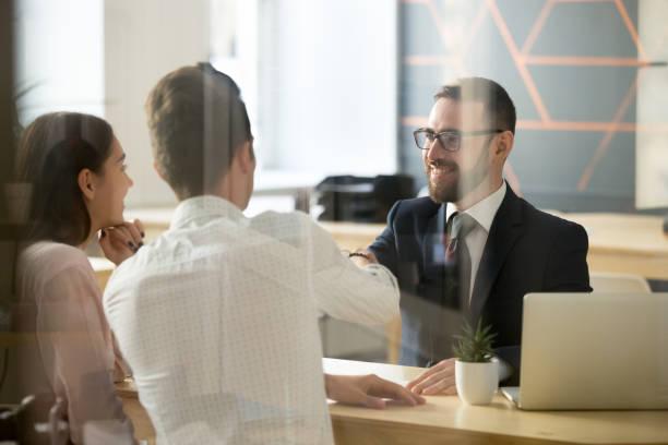 agente immobiliare maschio che fa stretta di mano ai clienti dopo il successo delle trattative in carica - banca foto e immagini stock