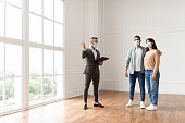 istock Male Realtor In Medical Mask Showing Buyers New Apartment 1326452516