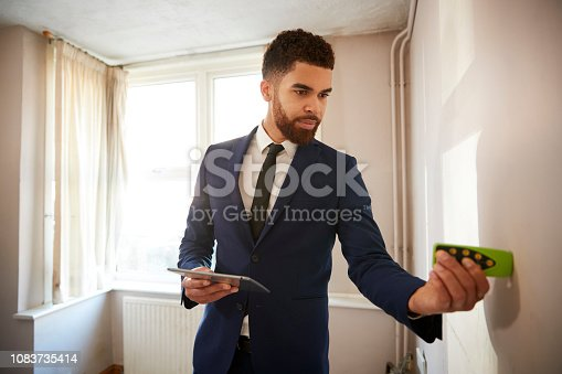 istock Male Realtor With Digital Tablet Measuring Room With Laser Measure 1083735414