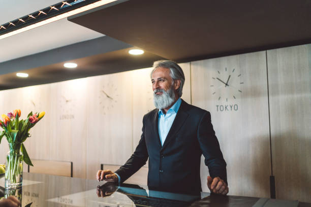 A male receptionist with gray hair and beard standing behind a hotel reception stock photo