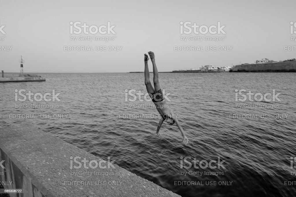 Male refugee dives into Aegean Sea in Greek Island harbor stock photo