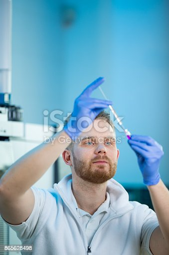 661098200istockphoto Male researcher carrying out scientific research in a lab 865628498