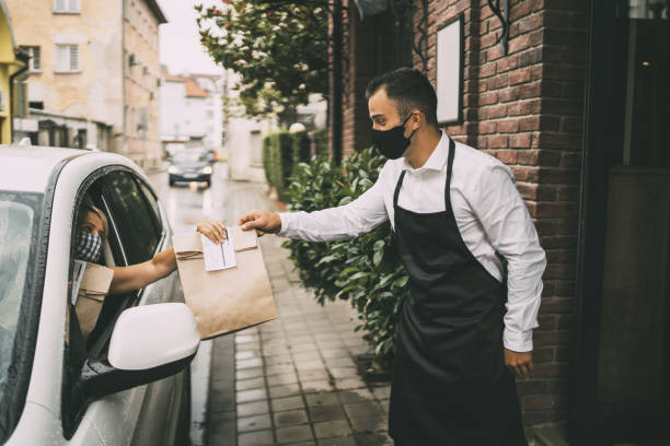Male restaurant employee delivers packed food to a female driver outside a restaurant. stock photo