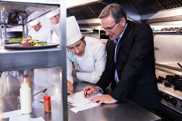 male restaurant manager writing on clipboard while interacting to head chef - kitchen counter imagens e fotografias de stock