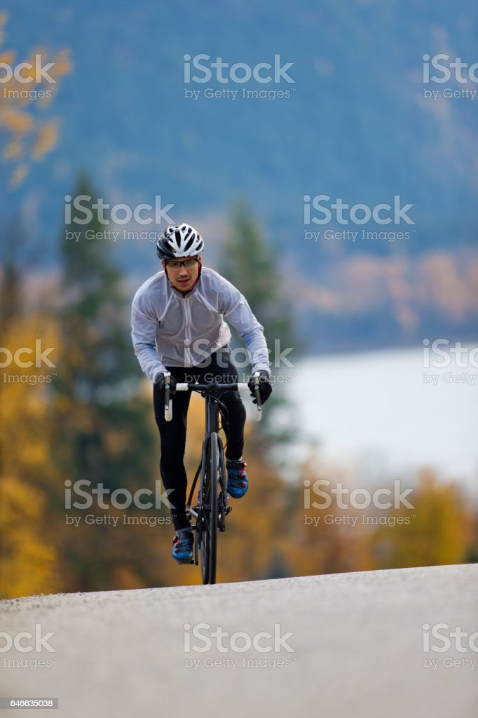 A male road cyclist rides up a quiet country road in British Columbia, Canada in the fall. stock photo
